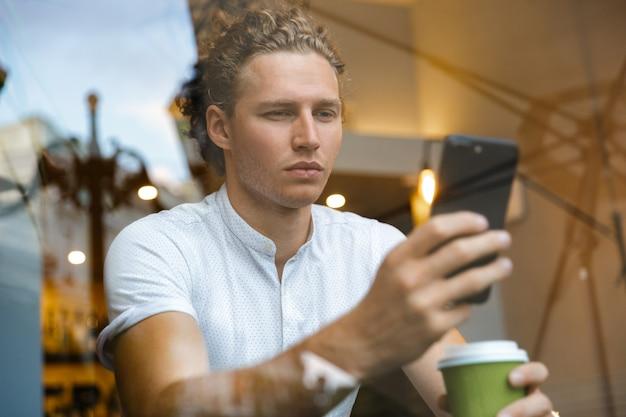 Ernstige gekrulde zakenman met behulp van smartphone en koffie drinken zittend aan tafel in café