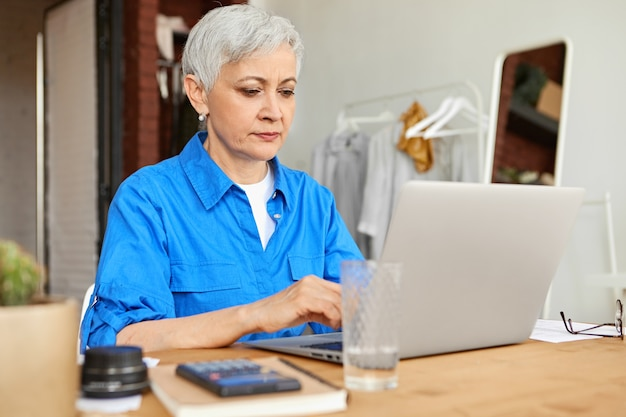 Ernstige gerichte huisvrouw van middelbare leeftijd gekleed in blauw shirt keyboarding op draagbare computer die elektriciteits-, gas- en nutsrekeningen online betaalt, zittend aan een bureau met rekenmachine. selectieve aandacht