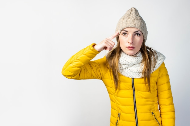 Ernstige gerichte jonge vrouw in een gele jas en hoed
