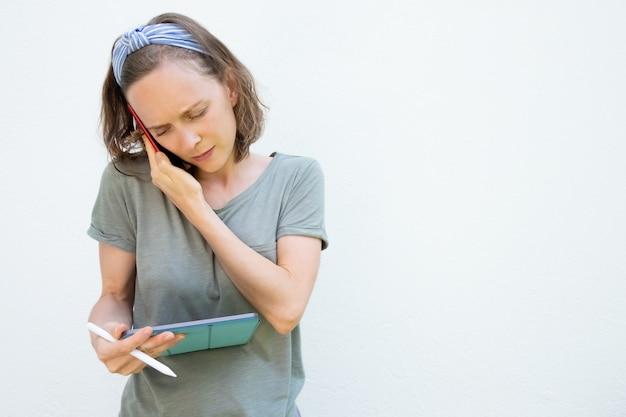 Ernstige gerichte jonge vrouw met behulp van tablet en pen
