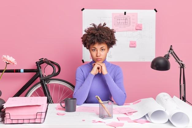 Ernstige geschoolde vrouwelijke werknemer met een donkere huid houdt handen onder de kin ziet er zelfverzekerd uit, poseert op het bureaublad met papierrollen en stickers verspreid over onderzoekt documenten in een gezellig thuiskantoor