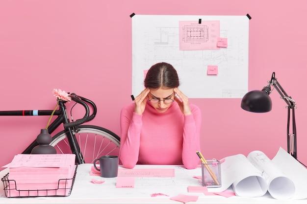 Ernstige getalenteerde jonge europese vrouwelijke architect die druk bezig is op haar werkplek, maakt een project van een nieuw wooncomplex geconcentreerd in papieren draagt een casual coltrui en probeert gedachten te verzamelen