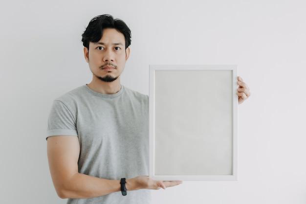 Ernstige gezicht man met een leeg frame geïsoleerd op een witte achtergrond