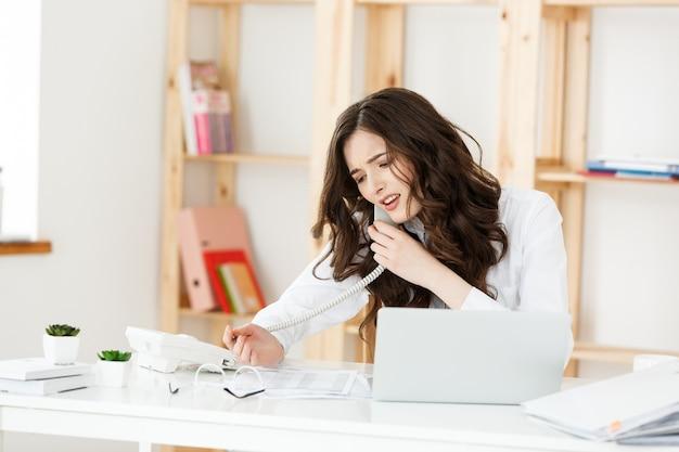 Ernstige goedgeklede verkoopster praten over de telefoon in kantoor achter haar bureau en laptop computer kopie ruimte