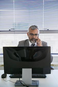 Ernstige grijze haren zakenman bellen op mobiele telefoon tijdens het gebruik van computer op de werkplek op kantoor. vooraanzicht. communicatie en multitasking concept