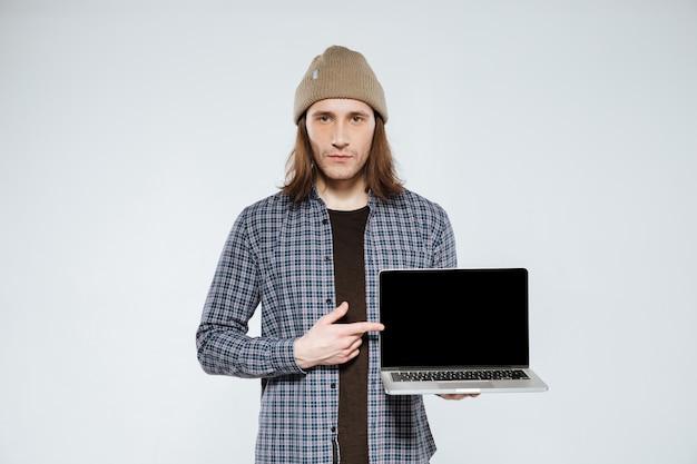 Ernstige hipster die het lege laptop scherm toont