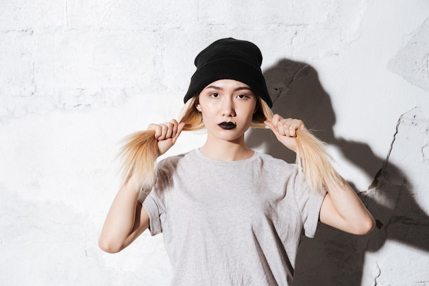 Ernstige hipster in zwarte hoed die haar haar houdt