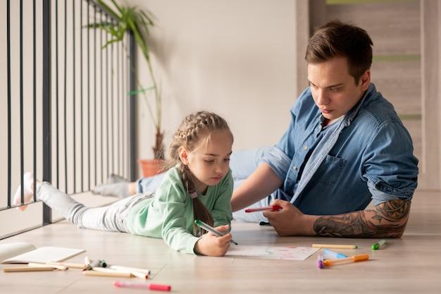 Ernstige hipster jonge vader in denim overhemd liggend op de vloer en advies geven aan dochter, klein meisje tekening foto met vader thuis