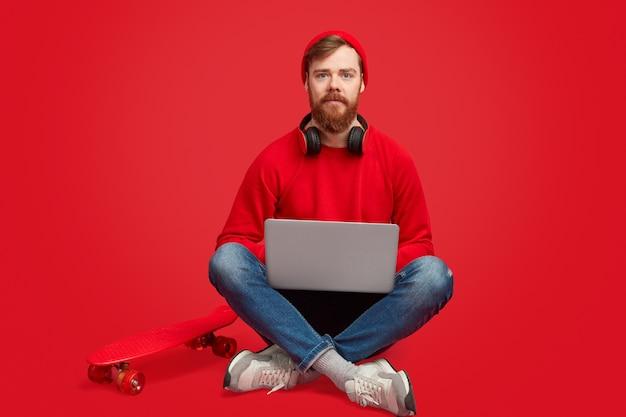 Ernstige hipster man met laptop en skateboard