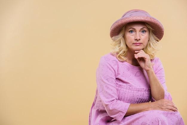 Ernstige hogere vrouw die een roze hoed draagt