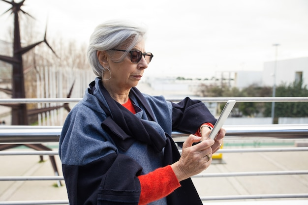 Ernstige hogere vrouw in zonnebril die tablet in openlucht gebruiken