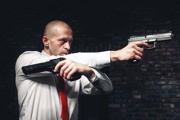 Ernstige huurmoordenaar in rode stropdas mikt met twee pistolen