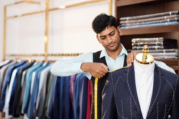 Ernstige indiase kleermaker die metingen doet van op maat gemaakte colbert op mannequin
