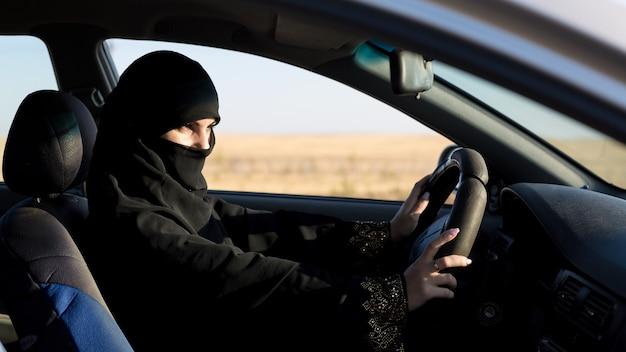Ernstige islamitische vrouwenbestuurder die weg w bekijkt