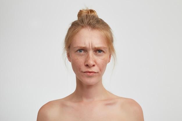 Ernstige jonge aantrekkelijke roodharige dame met natuurlijke make-up die haar lippen en fronsende wenkbrauwen tuit terwijl ze serieus kijkt, geïsoleerd over witte muur