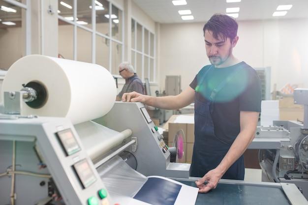 Ernstige jonge afdrukspecialist met baard die drukpers bedient tijdens het afdrukken van de testpagina in de fabriek