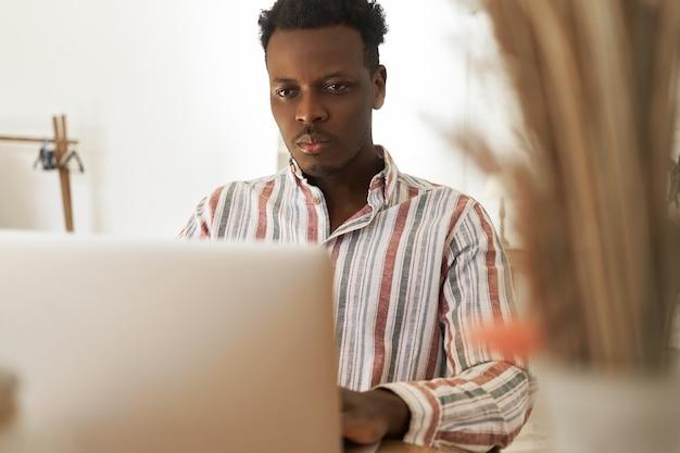 Ernstige jonge afrikaanse man studeert online op poartable computer, doet onderzoek of bereidt zich voor op een examen. geconcentreerde zwarte student kijkt webinar op laptop, verbetert vaardigheden op programmeren