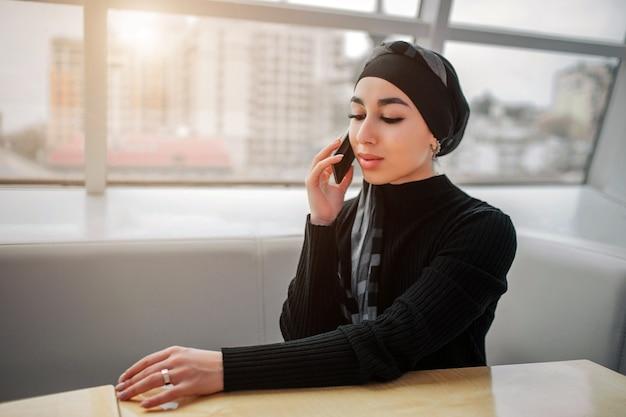 Ernstige jonge arabische vrouw zit binnen aan tafel en praat over de telefoon. ze kijkt naar beneden. de zon schijnt buiten.