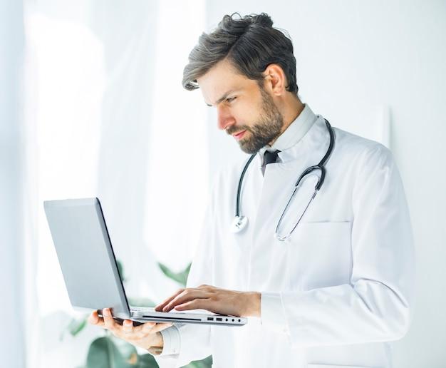 Ernstige jonge arts die laptop doorbladert