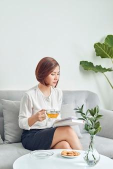 Ernstige jonge aziatische meisje in blouse en rok zittend op de bank en het drinken van thee tijdens het lezen van boek in de woonkamer