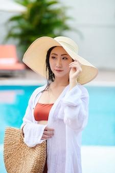Ernstige jonge aziatische vrouw in badkleding en wit overhemd die de zomerhoed aanpast en strozak draagt