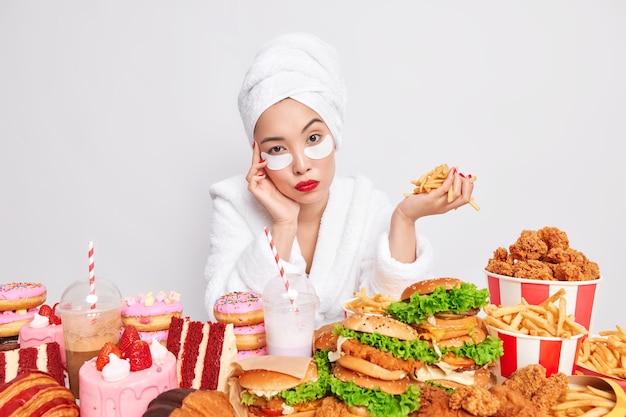 Ernstige jonge aziatische vrouw kijkt direct naar de camera omringd door fastfood