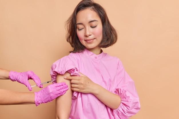 Ernstige jonge aziatische vrouw met donker haar gekleed in een roze blouse kijkt aandachtig naar het vaccinatieproces en krijgt een injectie in de arm geïsoleerd over een beige muur