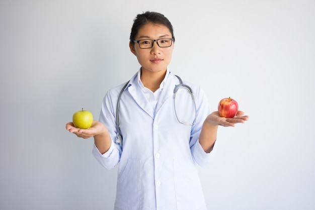 Ernstige jonge aziatische vrouwelijke arts die rode en gele appel houdt.