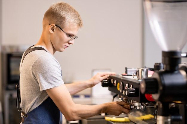 Ernstige jonge barista, de eigenaar van een klein gezellig café, gaat koffie zetten voor zijn klanten terwijl hij naast de werkplek staat