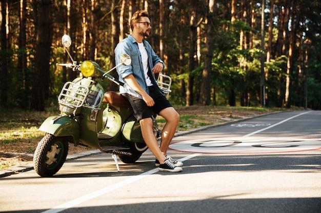 Ernstige jonge bebaarde man die in de buurt van scooter