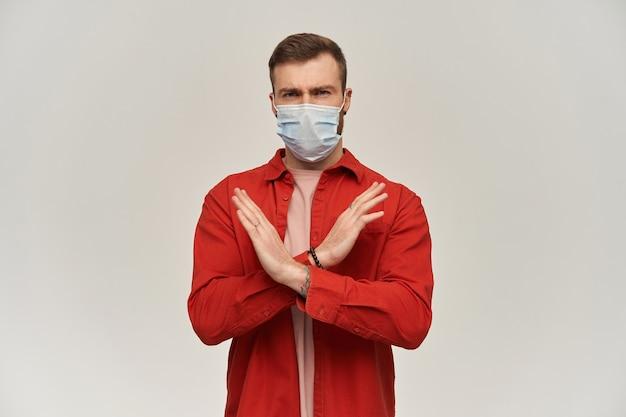 Ernstige jonge bebaarde man met virusbeschermend masker op gezicht tegen coronavirus maakt x-vorm met handen en armen en toont stopbord over witte muur