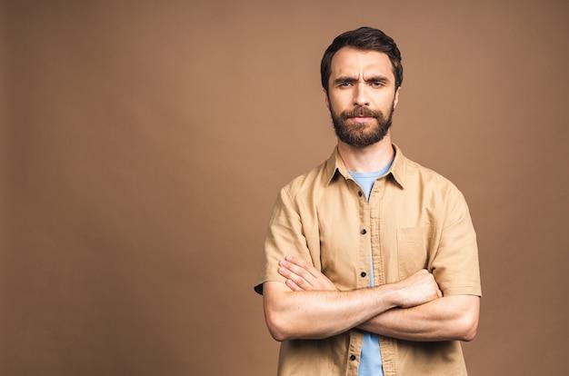 Ernstige jonge bebaarde man. portret van een knappe jongeman in casual gekruiste armen terwijl hij tegen een beige achtergrond staat.