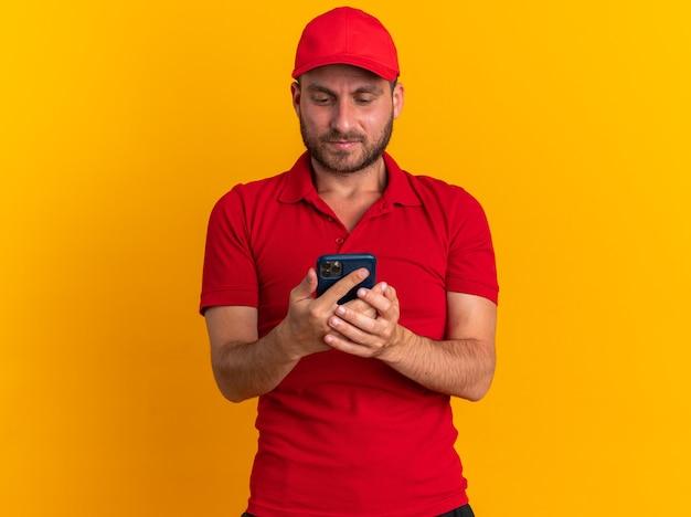 Ernstige jonge blanke bezorger in rood uniform en pet die mobiele telefoon vasthoudt en bekijkt geïsoleerd op oranje muur met kopieerruimte
