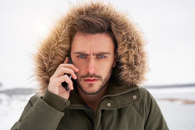 Ernstige jonge blanke man praten over de telefoon winter