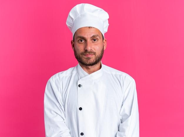 Ernstige jonge blanke mannelijke kok in uniform van de chef en pet kijkend naar camera geïsoleerd op roze muur