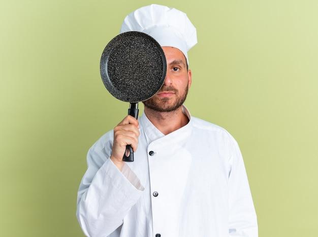Ernstige jonge blanke mannelijke kok in uniform van de chef-kok en dop die de helft van het gezicht bedekt met een koekenpan die naar de camera kijkt van erachter geïsoleerd op een olijfgroene muur