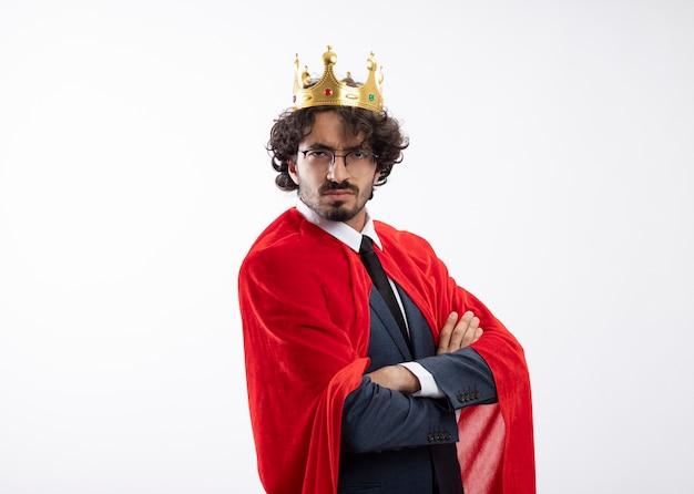Ernstige jonge blanke superheld man in optische bril met pak met rode mantel en kroon staat zijwaarts met gekruiste armen