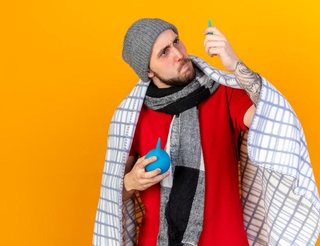Ernstige jonge blanke zieke man met muts en sjaal verpakt in geruite ruimen