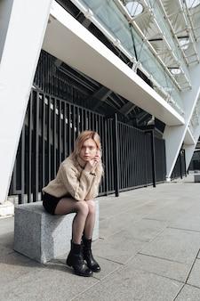 Ernstige jonge blonde dame buitenshuis
