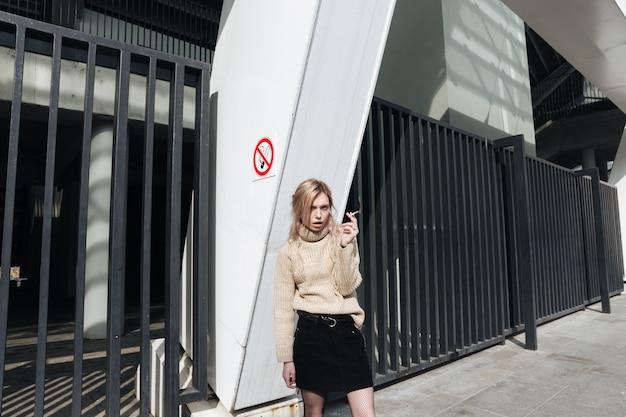 Ernstige jonge blonde dame met sigaret