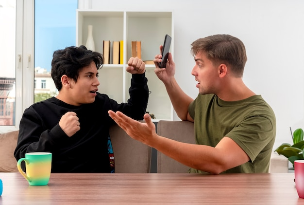 Ernstige jonge blonde knappe man houdt telefoon zittend aan tafel en kijken naar onaangename jonge brunette knappe jongen vuisten houden om te verdedigen in de woonkamer
