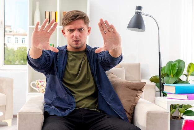 Ernstige jonge blonde knappe man zit op fauteuil gebaren hand stopbord met twee handen in de woonkamer