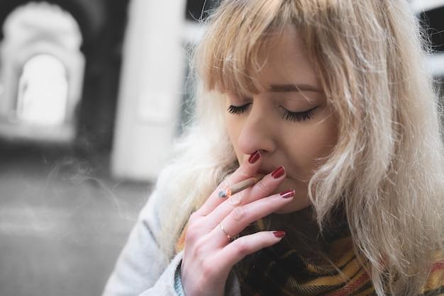 Ernstige jonge blonde vrouw op grijze achtergrond, roken met gesloten ogen