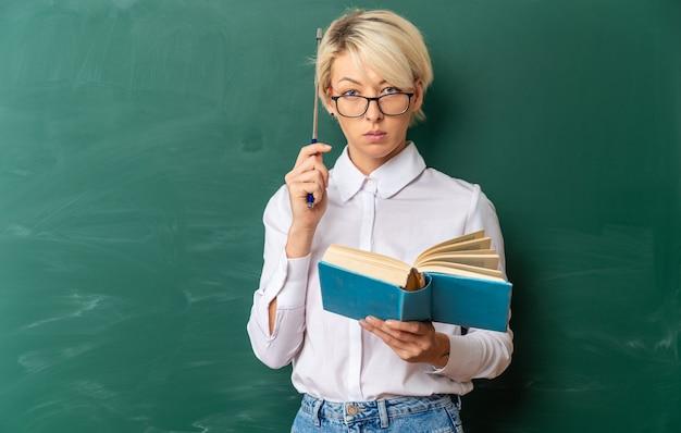 Ernstige jonge blonde vrouwelijke leraar met een bril in de klas die voor een schoolbord staat met een boek dat het hoofd aanraakt met de aanwijzerstok en kijkt naar de voorkant met kopieerruimte