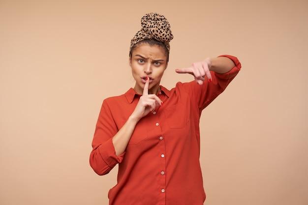 Ernstige jonge bruinharige dame fronst haar wenkbrauwen en wijst met wijsvinger naar voren, vraagt om stil te zijn terwijl ze over beige muur staat