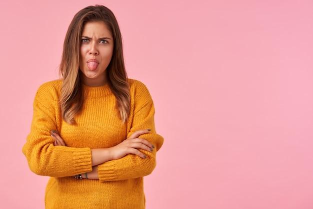 Ernstige jonge bruinharige dame in vrijetijdskleding die gezichten trekt en haar tong uitsteekt terwijl zij op roze staat, handen op haar borst kruist
