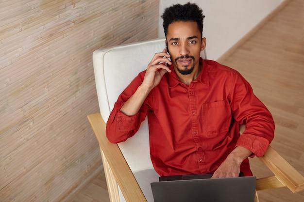 Ernstige jonge bruinogige kortharige gekrulde donkere man die aandachtig kijkt terwijl hij belt met zijn smartphone, zittend in een stoel op interieur