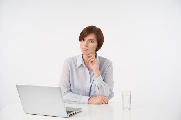 Ernstige jonge bruinogige kortharige vrouw met natuurlijke make-up houden opgeheven hand onder haar kin en peinzend kijken met gevouwen lippen, zittend aan tafel op wit