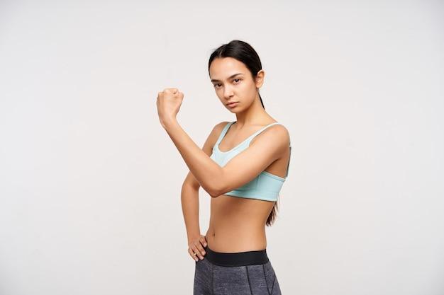 Ernstige jonge bruinogige langharige brunette vrouw hand opsteken terwijl ze sterke biceps toont en ernstig naar voren kijkt, geïsoleerd over witte muur