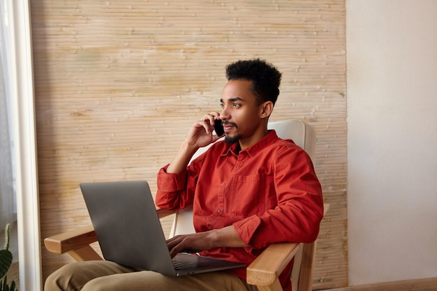 Ernstige jonge brunette bebaarde donkere huid freelancer bellen en peinzend uit raam kijken, zittend in een stoel op interieur met laptop op zijn knieën